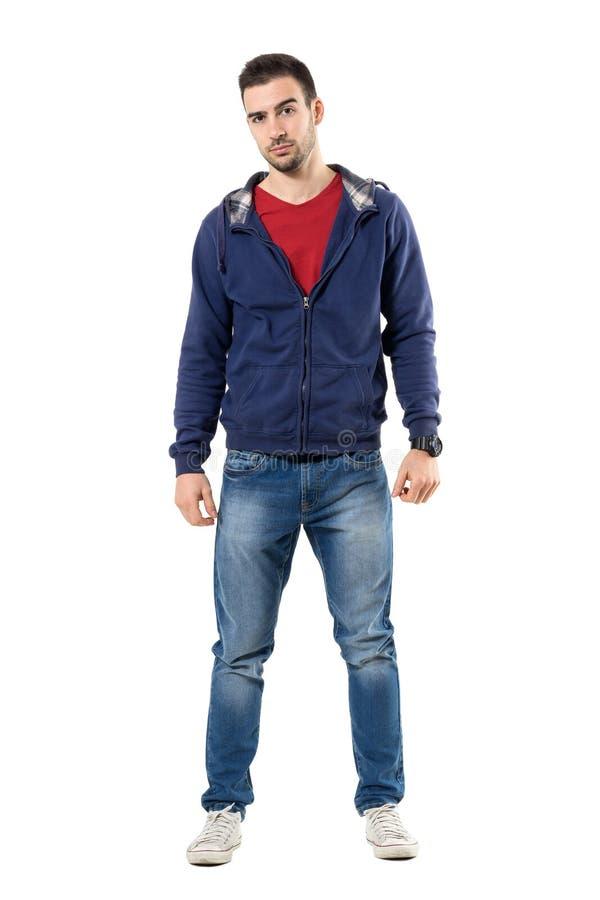 Gespannen jonge toevallige mens die in blauw sweatshirt met een kap camera sceptisch bekijken royalty-vrije stock foto