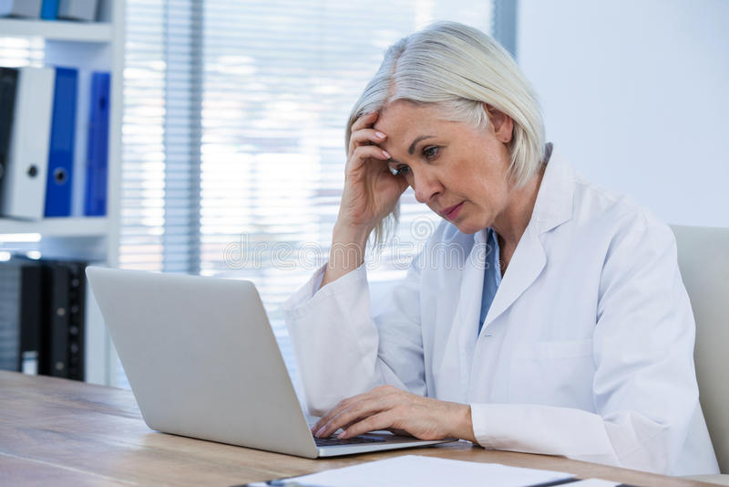 Gespannen vrouwelijke arts die aan haar laptop werken stock foto's