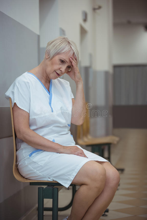 Gespannen vrouwelijke verpleegsterszitting op stoel in gang royalty-vrije stock afbeeldingen