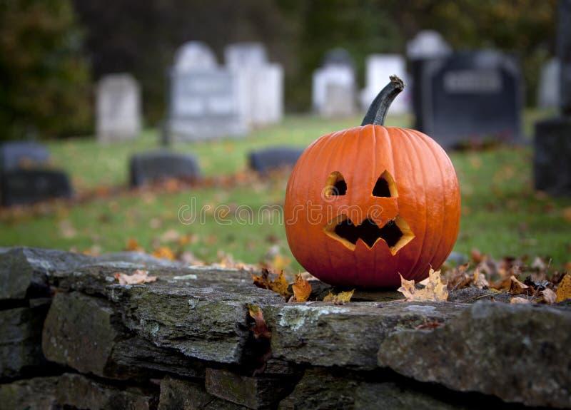 Gespenstischer Kürbis mit Friedhofhintergrund lizenzfreie stockbilder