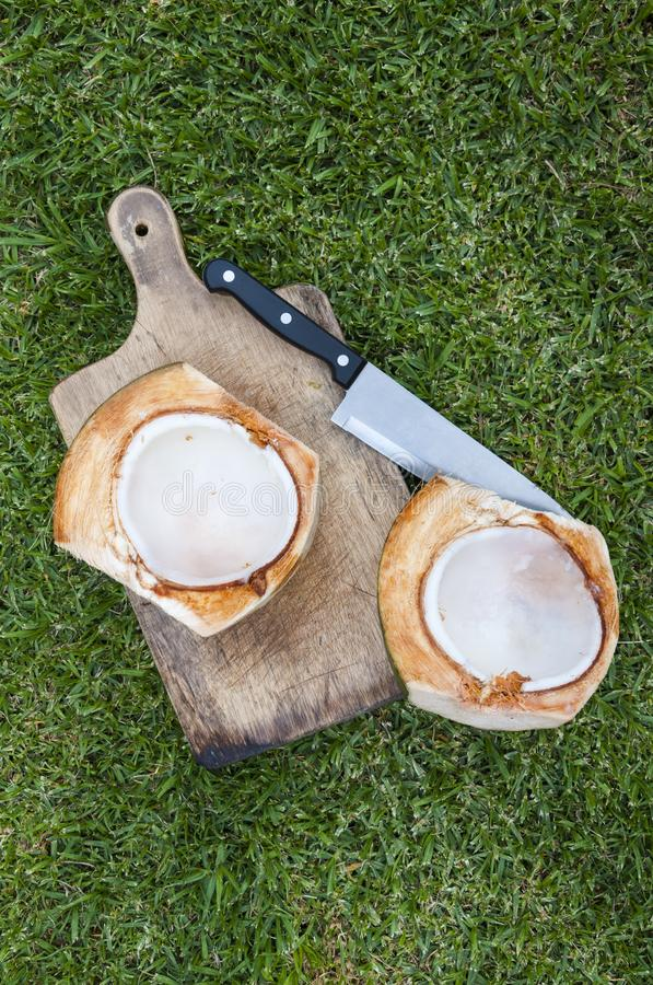 Gespleten kokosnoot en mes stock fotografie