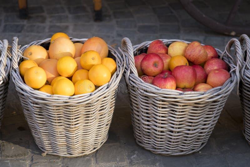 Gesponnene Körbe mit roten Äpfeln und Orangen stockbild