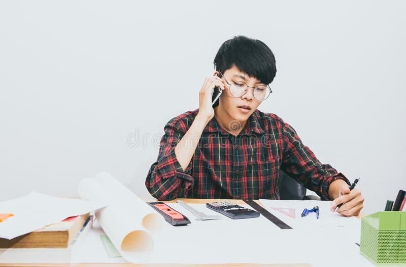 Gesprächs-Telefondruck des asiatischen Mannes sitzender auf dem Tisch lizenzfreies stockfoto