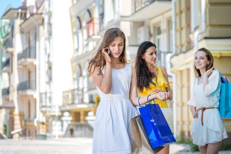 Gesprek met haar echtgenoot Drie meisjes die het winkelen zakken houden stock afbeelding