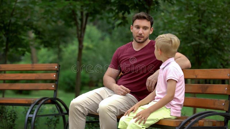 Gesprek tussen vader en zoon in park, houdende van papa die adviezen geven aan jong geitje royalty-vrije stock foto's