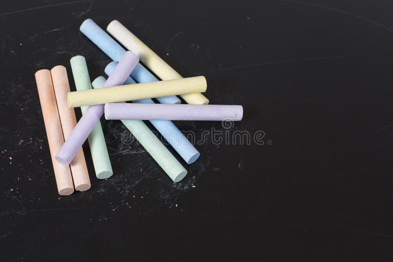 Gessi colorati assortiti su una lavagna o su un'ardesia fotografia stock