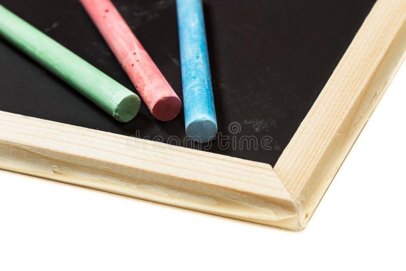 Gessi colorati e una lavagna fotografie stock