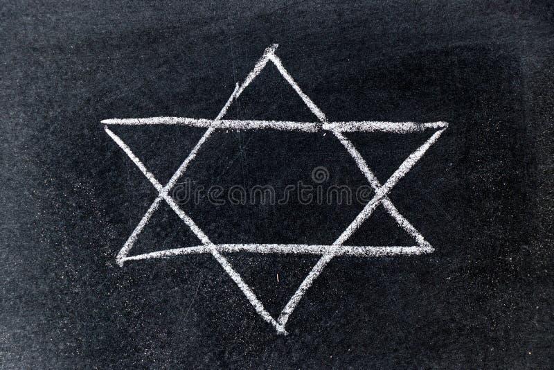Gesso bianco che assorbe forma della stella di Davide sul bordo nero immagini stock