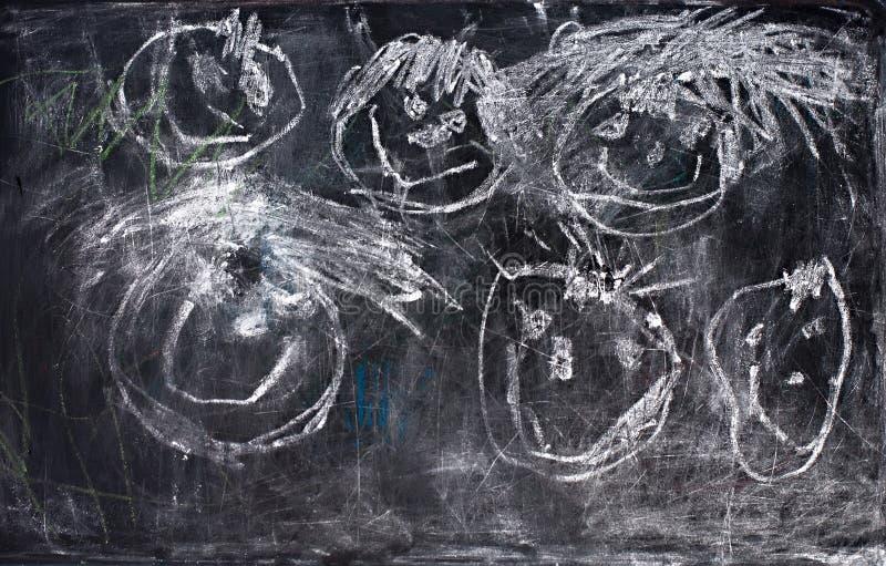 Gesso bianco del disegno dei bambini sulla lavagna immagine stock
