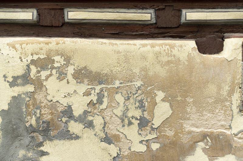 Gesso e pittura che pendono ad una casa a graticcio altrimenti meravigliosamente ristabilita su una via del ciottolo fotografia stock libera da diritti