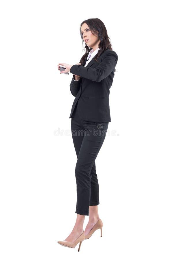 Gestörte Geschäftsfrau, die das Zeitholdingmobiltelefon wartet auf jemand überprüft stockfotos