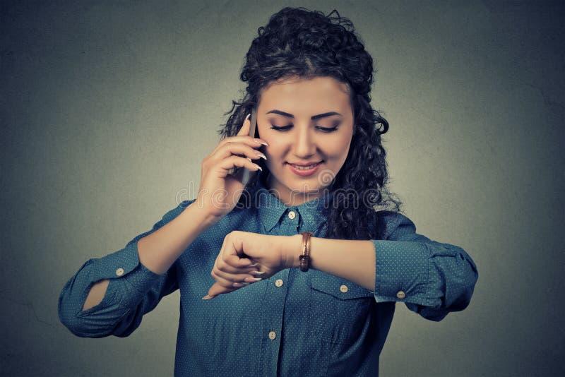 Gestão do negócio e de tempo Mulher feliz que olha o relógio de pulso, correndo tarde para encontrar-se foto de stock