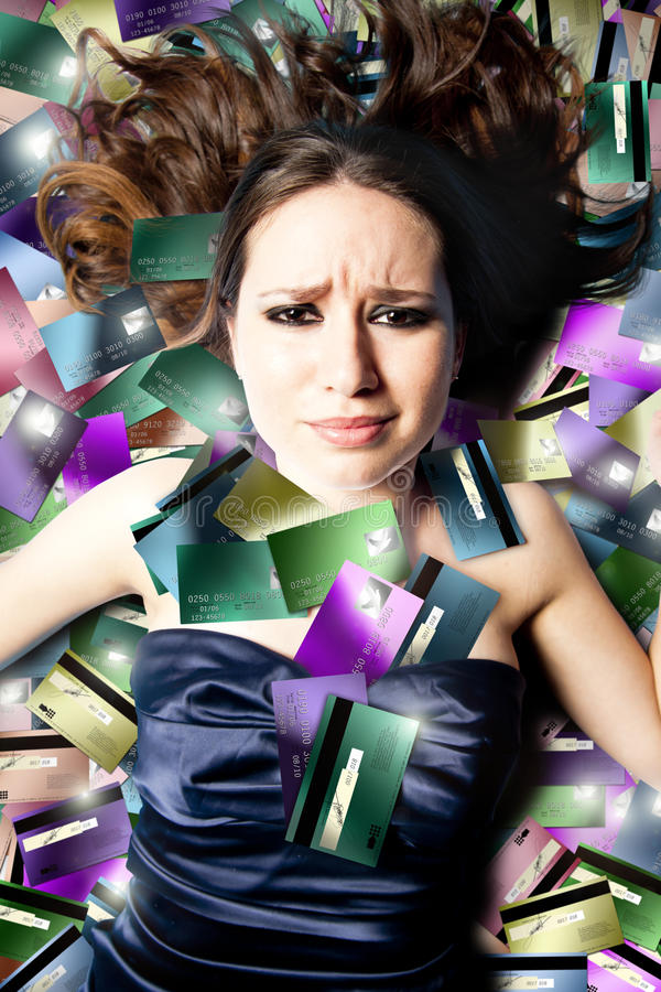 Gestörte Frau, die auf Kreditkarten liegt stockfotos