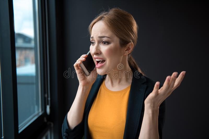 Gestörte Frau, die telefonisch sagt stockfotos