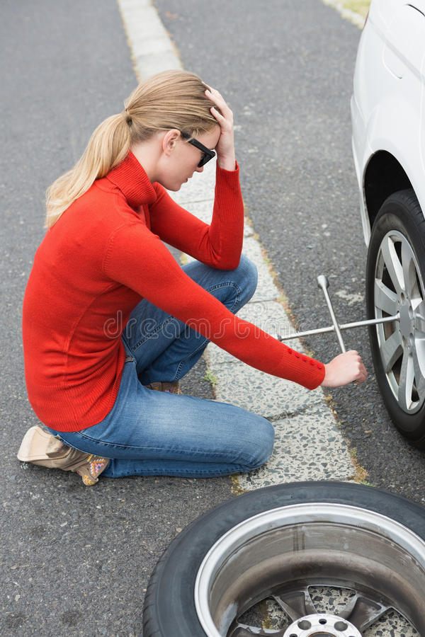 Gestörte Frau, die versucht, Reifen zu ersetzen stockbild