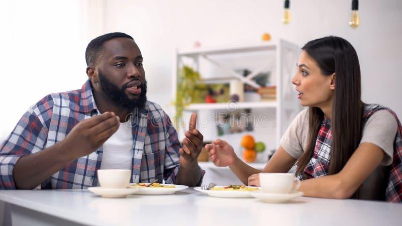 Gestörte gemischtrassige Paare, die während des Mittagessens, Familienbeziehungen, Konflikt streiten lizenzfreie stockfotos