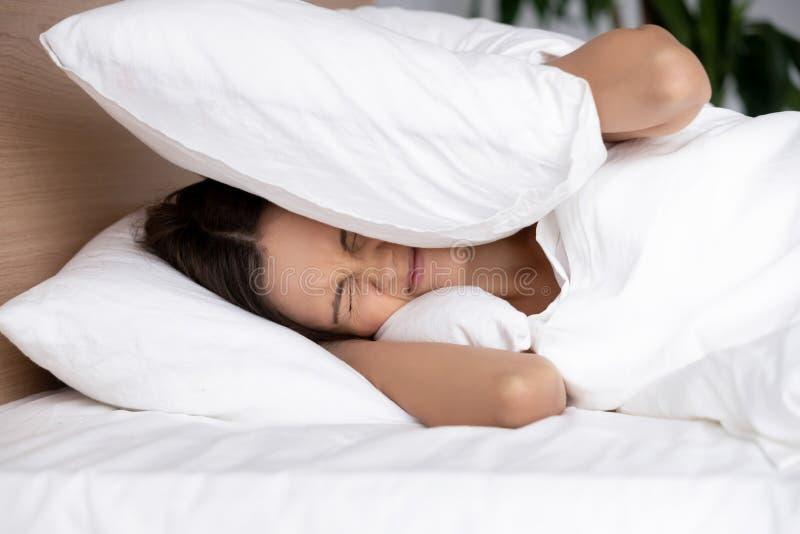 Gestörte junge Frau, die Ohren mit dem Kissen, leiden unter Geräuschen bedeckt stockfoto