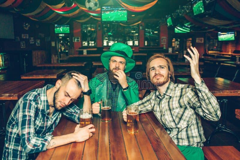 Gestörte junge Männer sitzen bei Tisch in der Kneipe Sie schauen vorwärts und passen auf Kerl auf mittleren Abnutzung St Patrick  stockfotos