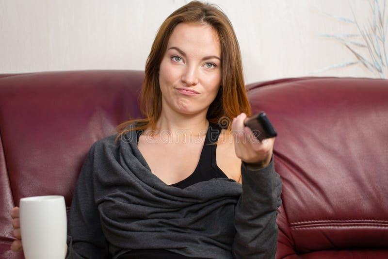 Gestörte schöne junge Frau, die Fernsehfernbedienung auf Couch verwendet stockfotografie