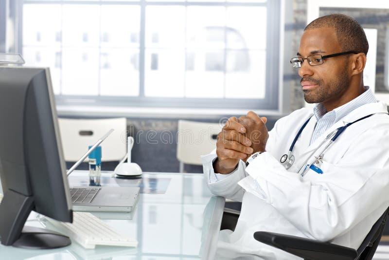 Gestörter Doktor, der am Schreibtisch sitzt lizenzfreie stockfotografie