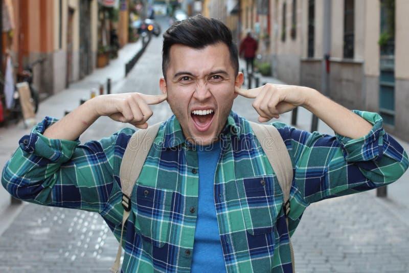 Gestörter Fußgänger, der seine Ohren bedeckt lizenzfreie stockfotos