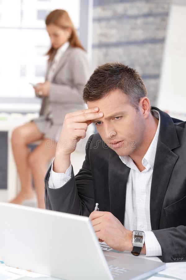 Gestörter Geschäftsmann, der an Laptop arbeitet lizenzfreie stockfotos