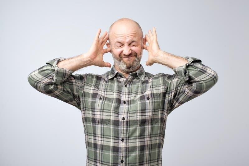 Gestörter reifer Mann, der Ohren mit den Fingern verstopft stockfotografie