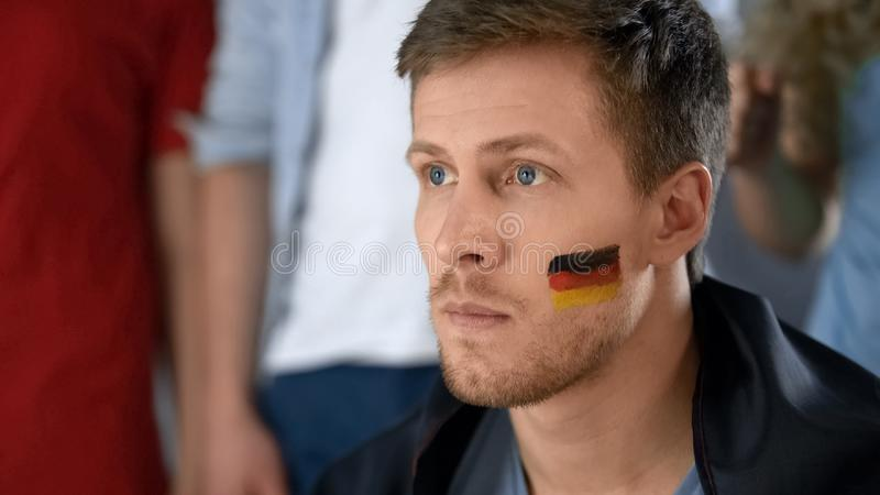 Gestörtes deutsches Fußballfan enttäuscht über Niederlage, aufpassendes Spiel mit Freunden lizenzfreie stockfotografie