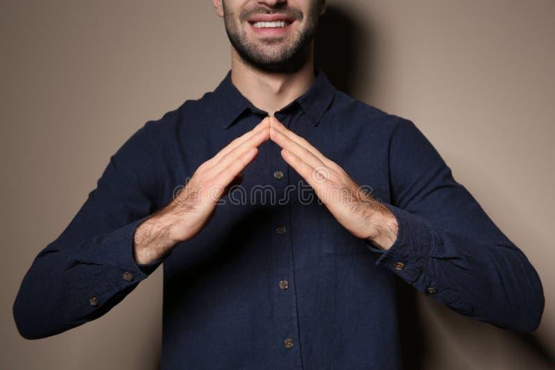 Gest för manvisningHUS i teckenspråk på färgbakgrund royaltyfria bilder