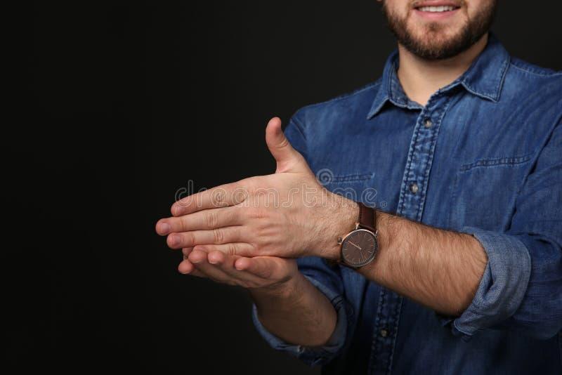 Gest för manvisningSTOPP i teckenspråk på svart bakgrund arkivbilder