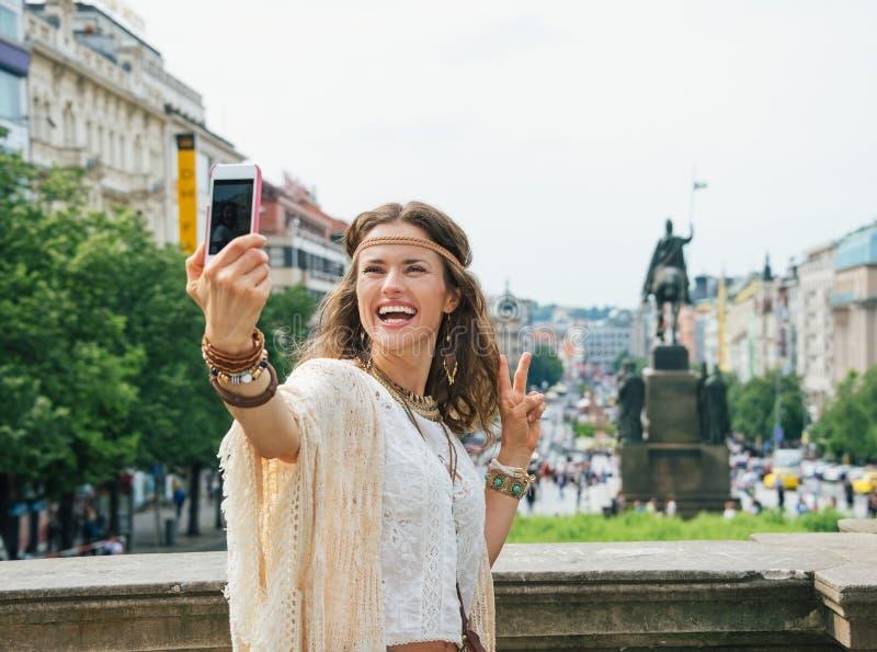 Gest för seger för hippiekvinnavisning och danandeselfie i Prague royaltyfri foto