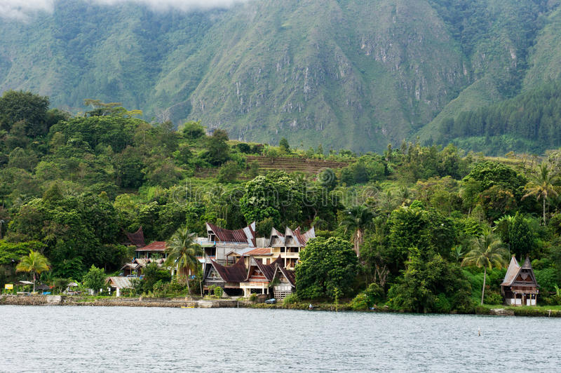 Gestalt einiger Häuser am Fuß eines Berges nahe bei einem See in Insel Sumatras Samosir stockbild