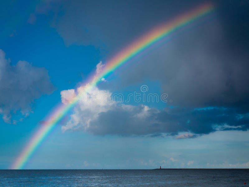 Gestalten Sie Ansicht über Himmel mit Regenbogen in Meer landschaftlich stockfoto