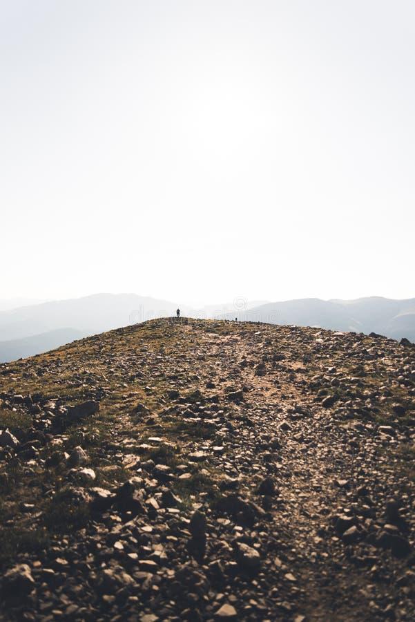 Gestalten Sie Ansicht einer Person landschaftlich, die in Richtung zur Spitze der Dilemma-Spitze geht stockbilder