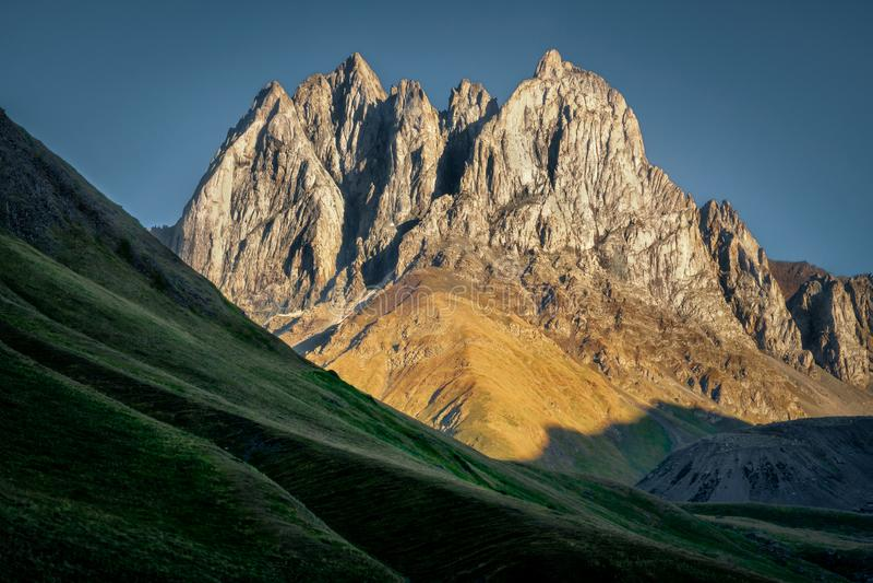 Gestalten Sie Ansicht von Bergspitzen und von Wiesen in Kazbegi, Land von Georgia landschaftlich stockbild