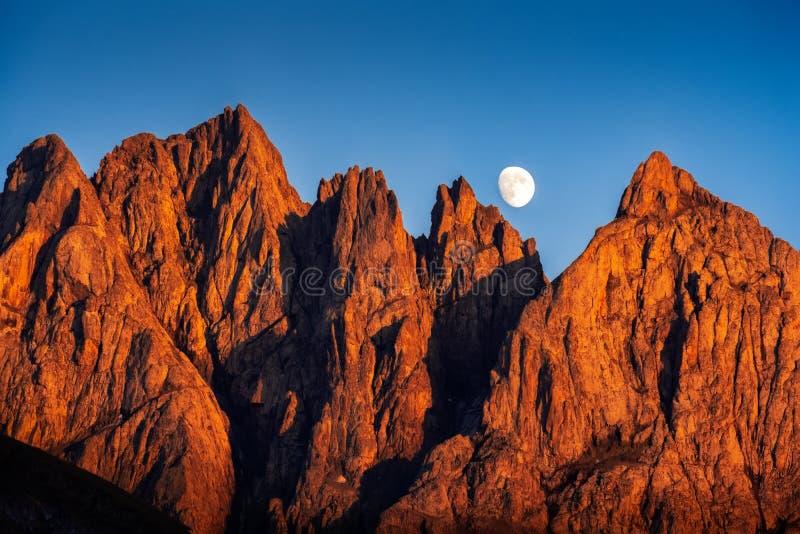 Gestalten Sie Ansicht von bunten Bergspitzen bei Sonnenuntergang mit steigendem Mond landschaftlich stockbild
