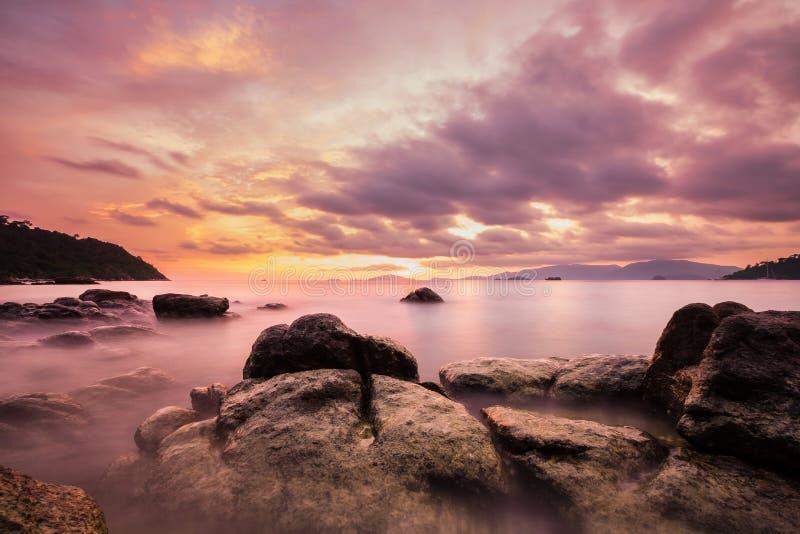 Gestalten Sie auf der Insel, bunter langer Belichtungsozean, Weinlesetonweichzeichnung, im Sonnenuntergang mit erstaunlichem Himm lizenzfreie stockfotos