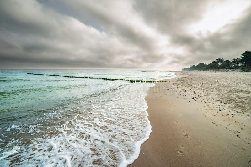 Gestalten Sie, bewölkter Himmel, Meer, breakewater, Strand landschaftlich lizenzfreie stockbilder
