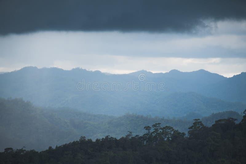 Gestalten Sie Bild von Grünregenwaldhügeln am regnerischen Tag mit bewölktem Himmel landschaftlich stockfoto
