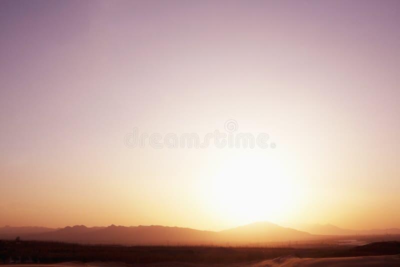 Gestalten Sie den Schuss der Sonne unten kommend über die Berge in der Wüste, klarer Himmel, China landschaftlich stockfotos