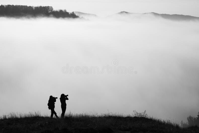 Gestalten Sie Fotografen auf dem Feld am nebelhaften Morgen landschaftlich stockbilder