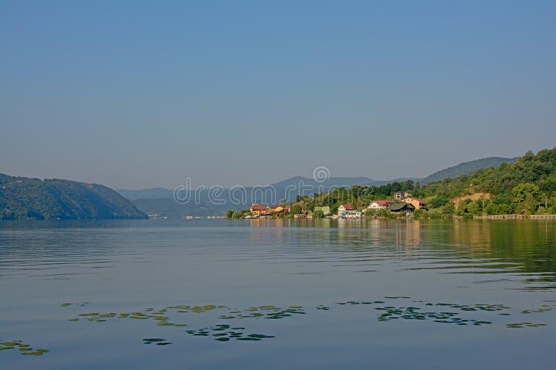 Gestalten Sie mit Bergen und Dorf auf den Dämmen von Fluss Donau, Rumänien im Licht des frühen Morgens landschaftlich lizenzfreies stockbild