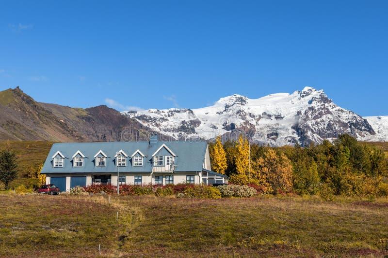 Gestalten Sie mit einem isländischen Haus und schneebedeckten Bergen in der Rückseite landschaftlich stockfotografie