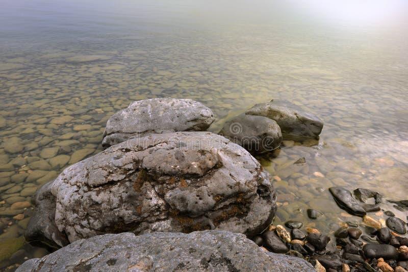 Gestalten Sie mit einem steinigen Ufer auf dem See landschaftlich Große Steine im klaren klaren Wasser stockfotografie