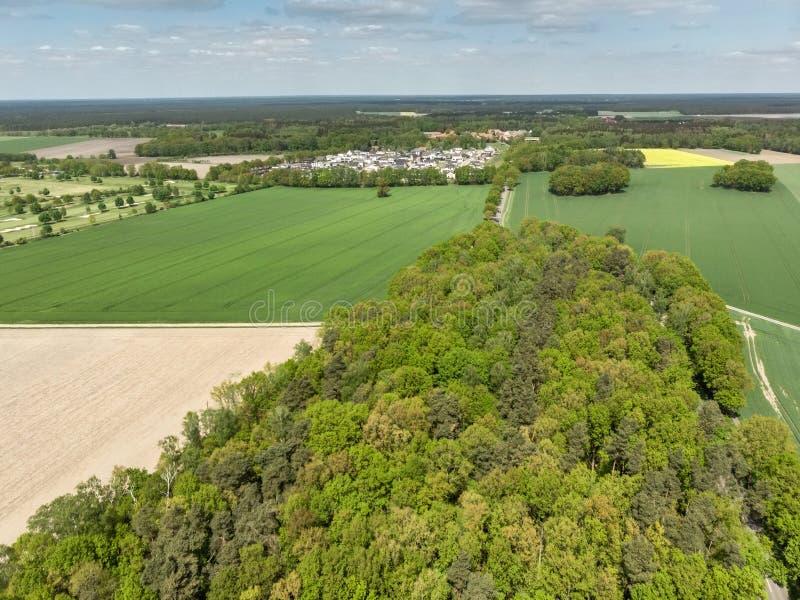 Gestalten Sie mit einem Wald, Wiesen und Felder und ein kleines Dorf im Hintergrund, Vogelperspektive von einer Höhe von 100 Mete lizenzfreie stockfotografie