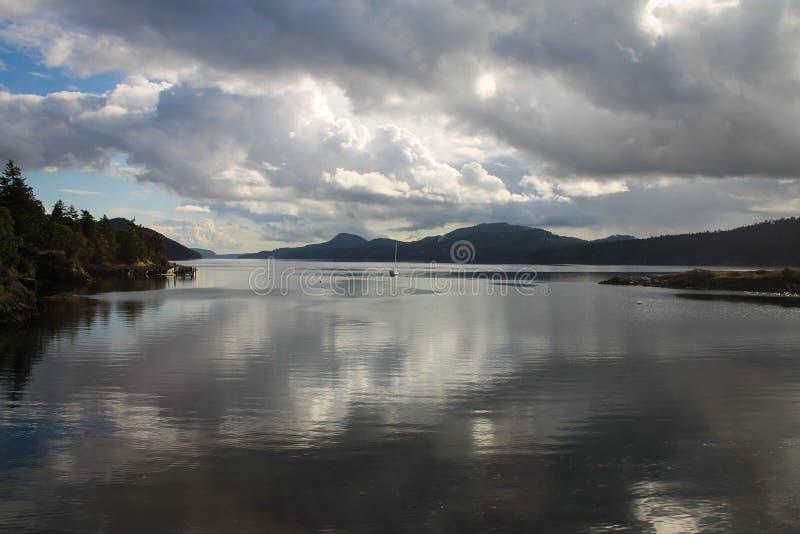 Gestalten Sie mit ruhigen Wasser u. Segelboot im Abstand und großem, ausdehnendem Himmel mit den geschwollenen Kumuluswolken land stockbild