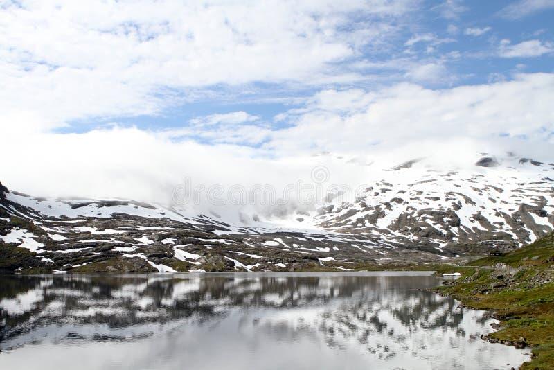 Gestalten Sie mit Schnee, Gebirgssee und Reflexion landschaftlich stockfotografie