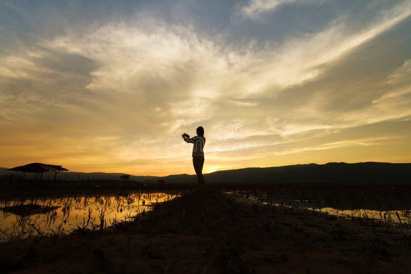 Gestalten Sie Naturszene von den Frauen landschaftlich, die das Foto auf drastischen Himmel schießen stockfoto
