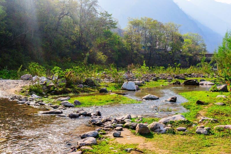 Gestalten Sie Schuss mit kleinen Flusshügeln und -sonnenlicht während des mornin landschaftlich stockfoto