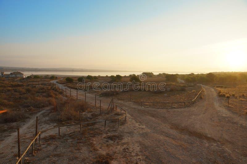Gestalten Sie von der Höhe an der Dämmerung über dem See, die Straße geht hinter das Feld mit einem Zaun landschaftlich stockfotos